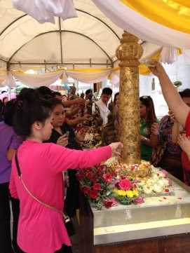Pouring water and scented oils over Buddha statues and holy carvings
